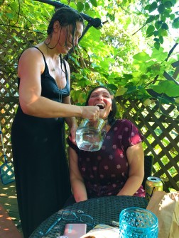 Hannah Rose pouring water on Lindsey on a hot summer day