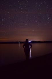naked woman staring out at lake superior